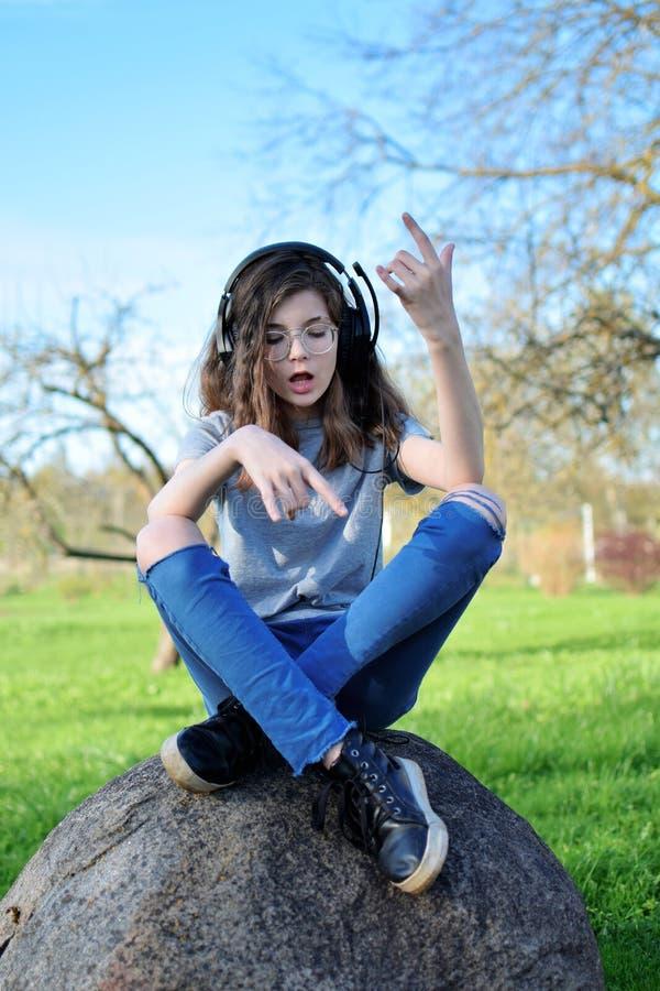 女孩听的音乐和唱歌 免版税库存图片