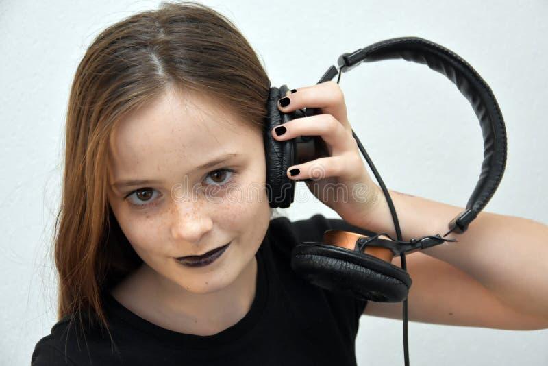 女孩听的音乐通过耳机 免版税库存图片