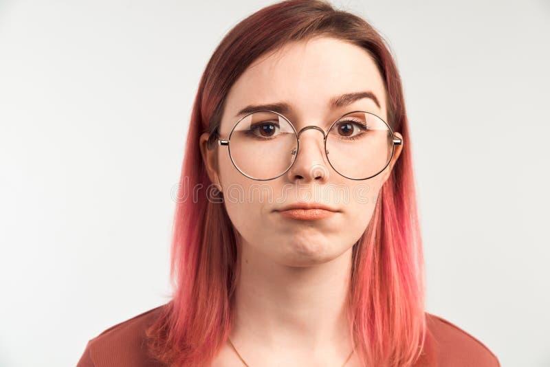 女孩听见重要信息,抬在触目惊心的一眼眉 俏丽的妇女照片有严肃的神色在照相机 免版税库存图片