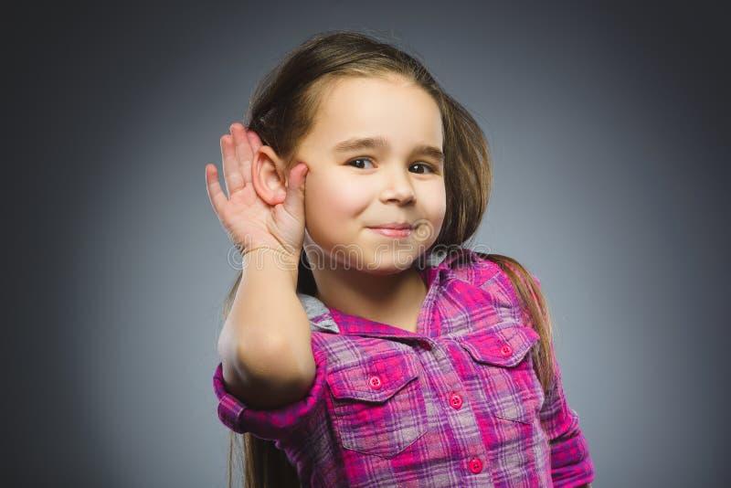 女孩听 儿童听力某事,对耳朵姿态的手在灰色背景 免版税库存图片