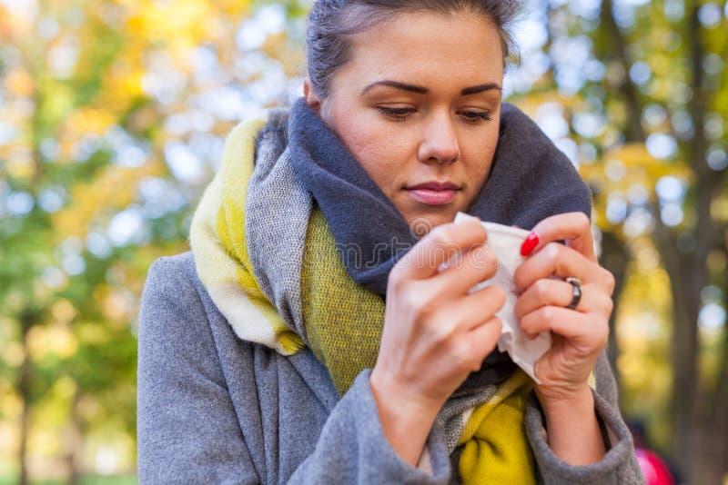 女孩吹她的鼻子 她是冷的 秋天时间 免版税库存照片