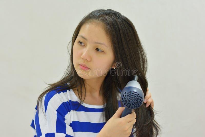 女孩吹干燥她的有hairdryer的头发 免版税库存照片
