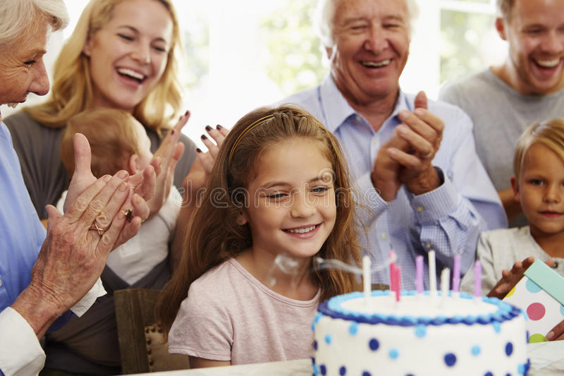 女孩吹灭生日蛋糕蜡烛在家庭党 库存照片