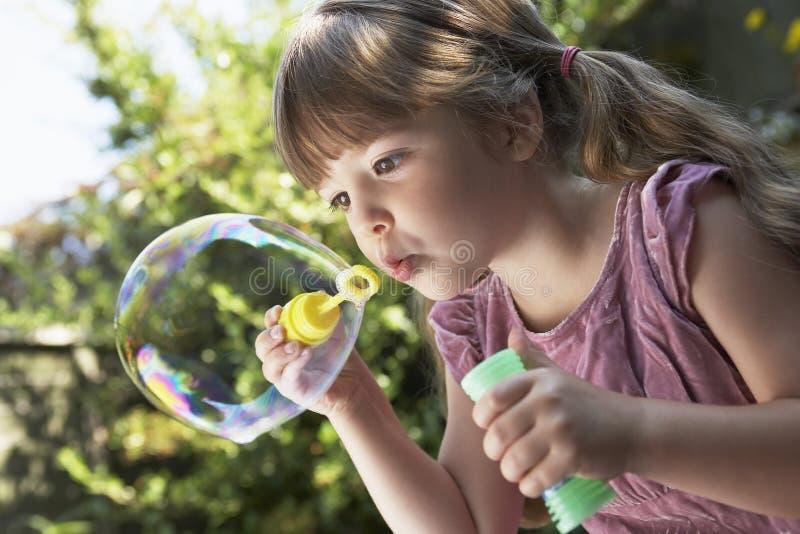 女孩吹的肥皂泡在后院 免版税图库摄影