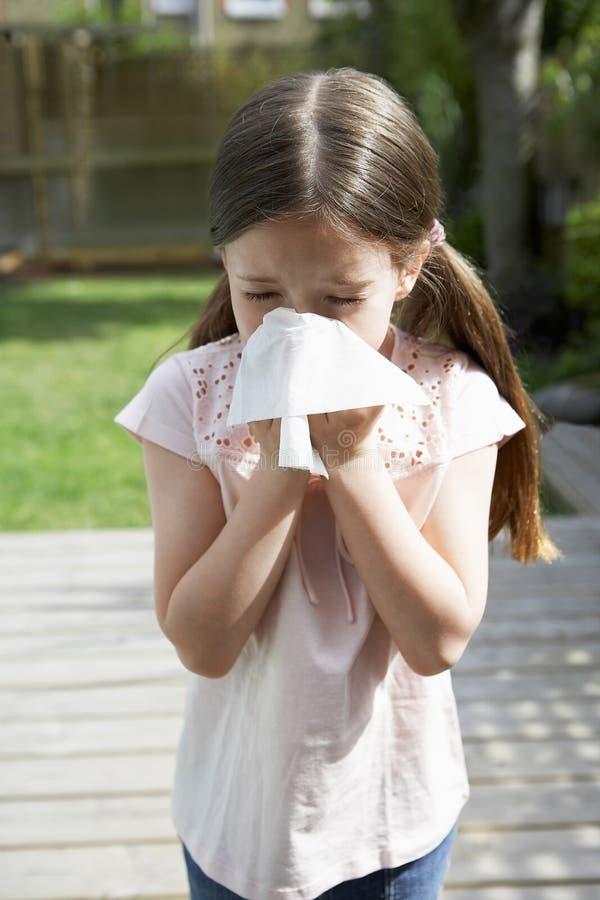 女孩吹的鼻子在后院 库存照片