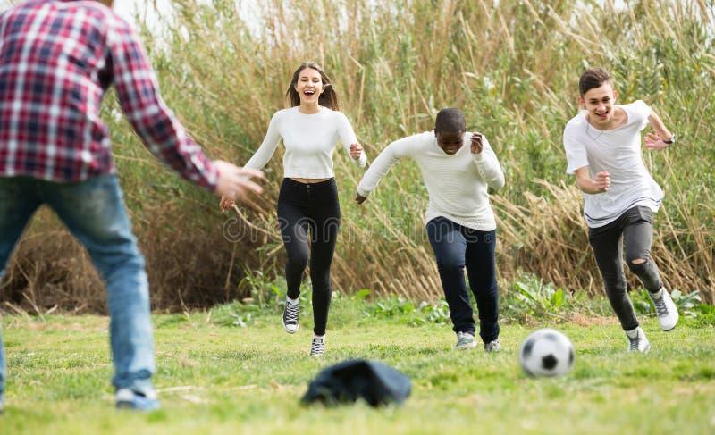 女孩和三个男孩在春天公园和微笑的踢橄榄球 图库摄影