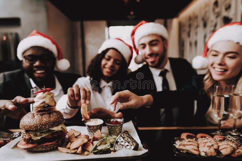女孩和人 汉堡 帽子s圣诞老人 在新人的白人妇女的背景愉快的查出的人 免版税库存照片