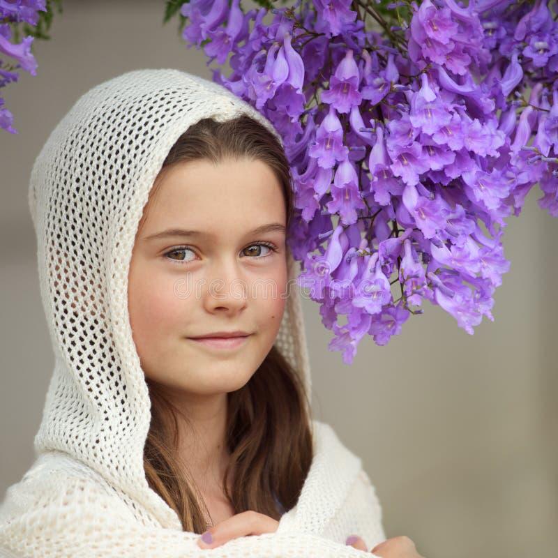 女孩和兰花楹属植物树 免版税图库摄影