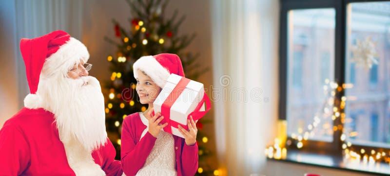 女孩和圣诞老人有圣诞节礼物的在家 免版税库存照片
