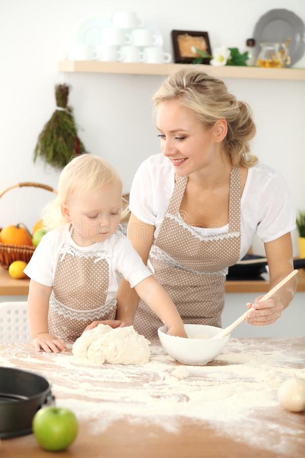 女孩和她白肤金发的妈妈笑米黄的围裙的使用和,当揉面团在厨房里时 r 库存照片