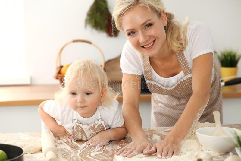 女孩和她白肤金发的妈妈笑米黄的围裙的使用和,当揉面团在厨房里时 r 免版税库存照片