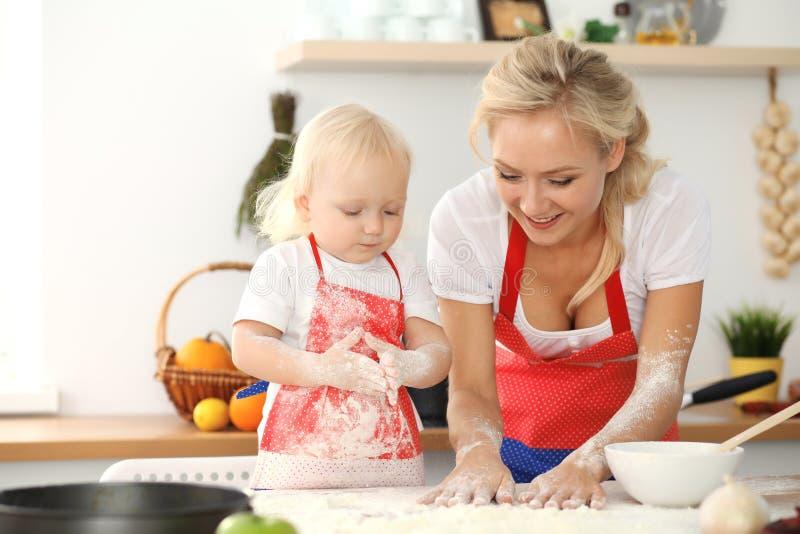 女孩和她白肤金发的妈妈笑红色的围裙的使用和,当揉面团在厨房里时 r 库存图片