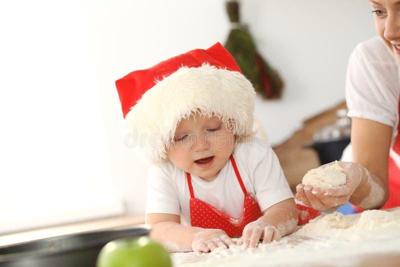 女孩和她白肤金发的妈妈笑红色的围裙的使用和,当揉面团在厨房里时 r 库存照片