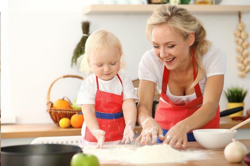 女孩和她白肤金发的妈妈笑红色的围裙的使用和,当揉面团在厨房里时 r 免版税库存图片
