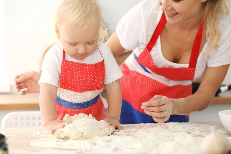 女孩和她白肤金发的妈妈笑红色的围裙的使用和,当揉面团在厨房里时 r 免版税图库摄影