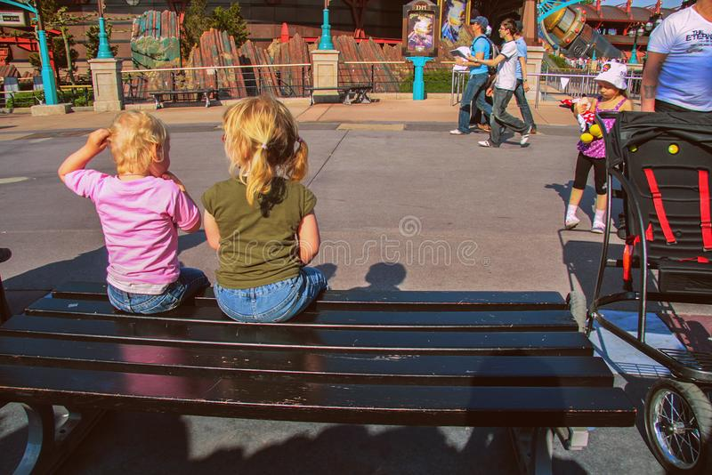 女孩和她的兄弟坐长凳 在欧洲附近的旅行 愉快的滑稽的家庭 库存图片