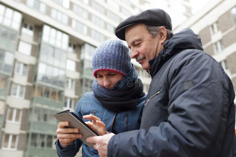 女孩和她的父亲有一种片剂的在寻找正确的手上在城市 免版税图库摄影