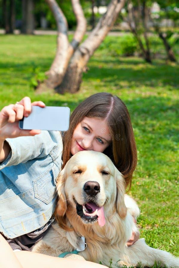 女孩和她的狗selfie夏天在绿草背景  免版税库存照片