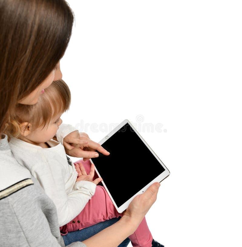女孩和她美丽的年轻妈妈使用一种数字片剂 免版税库存图片