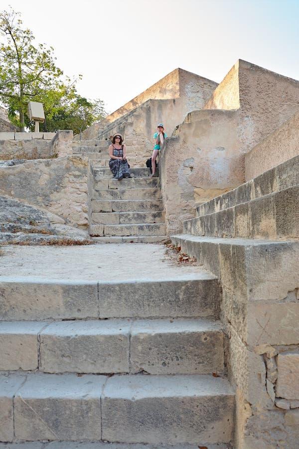 女孩和妇女坐石灰石,阿利坎特,西班牙老黄色石楼梯在圣塔巴巴拉城堡的 免版税库存照片