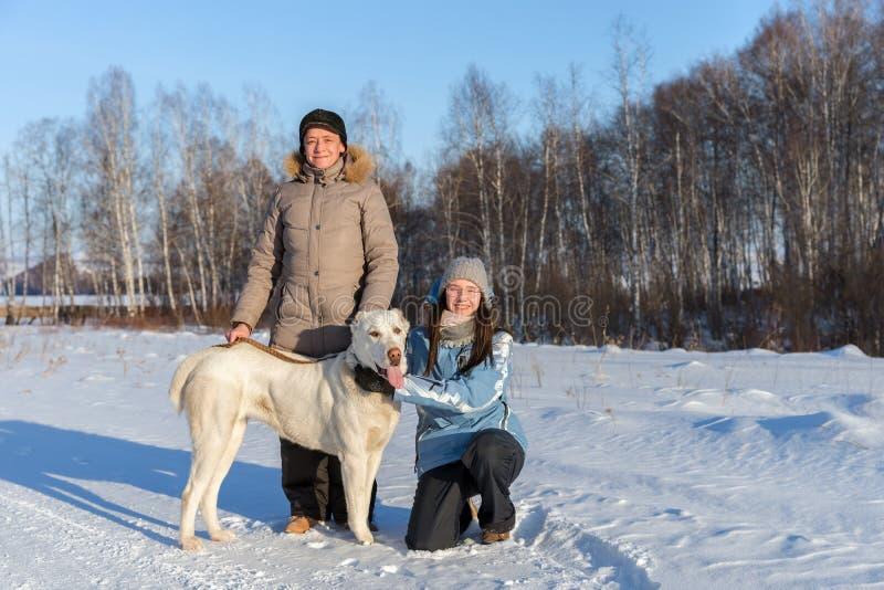 女孩和妇女有一只大白色牧羊犬的在路一边在森林中 图库摄影