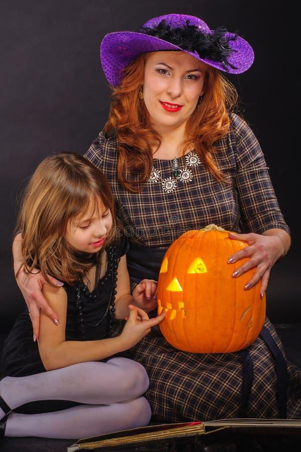 女孩和成熟母亲在万圣夜集会 库存图片
