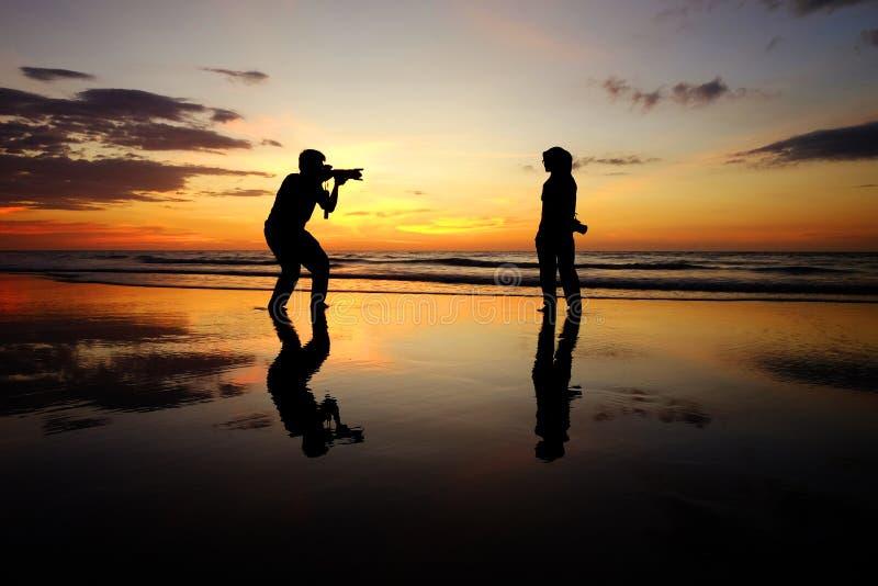 女孩和摄影师剪影在日落期间 免版税图库摄影