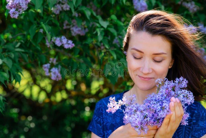 女孩和淡紫色花花束 库存照片