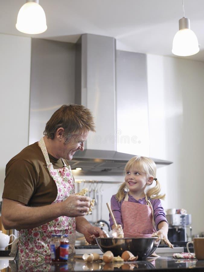 女孩和父亲烘烤在厨房里 库存图片