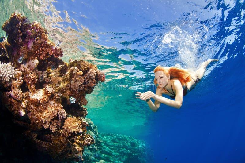 女孩和珊瑚在海 免版税图库摄影