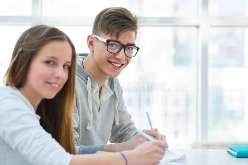 女孩和男孩一起学习并且帮助其中每一 免版税库存图片