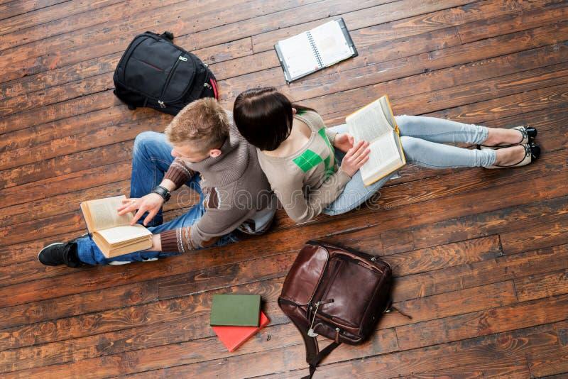 女孩和男孩倾斜在彼此的阅读书在木地板上 免版税库存图片