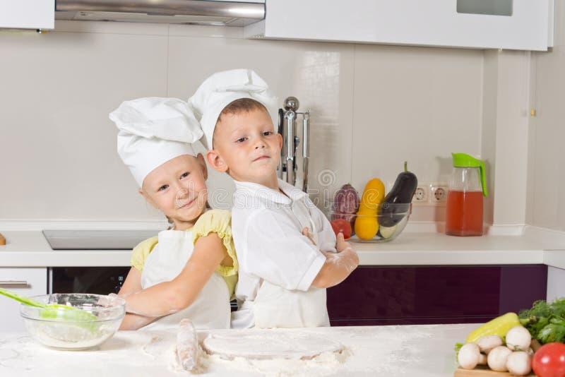 女孩和男孩在厨房里,紧接摆在 免版税库存照片