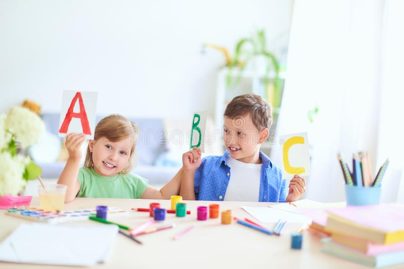 女孩和男孩在家学会 愉快的孩子在与学校用品微笑滑稽和学会字母表的桌上在a 免版税库存图片