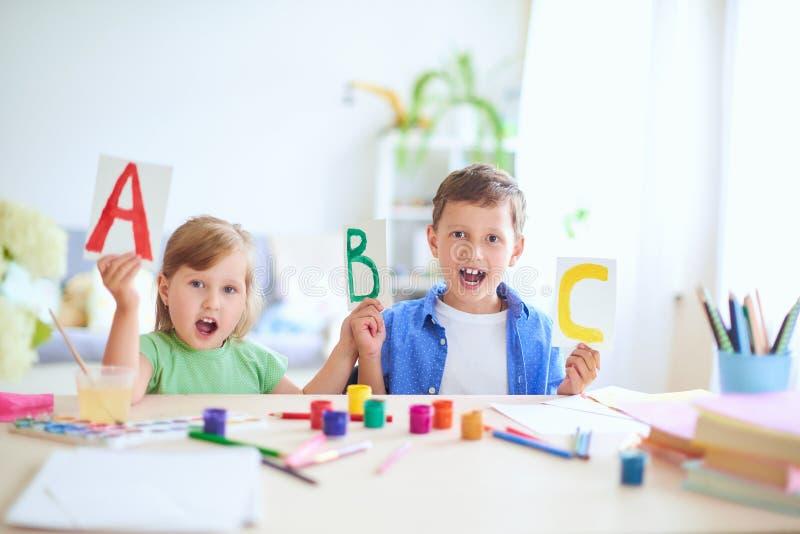 女孩和男孩在家学会 愉快的孩子在与学校用品微笑滑稽和学会字母表的桌上在a 免版税图库摄影