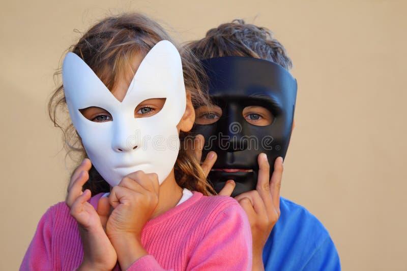 女孩和男孩在屏蔽之后的隐藏表面 库存照片