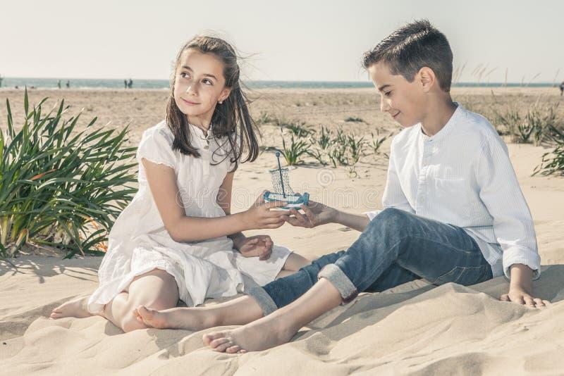 女孩和男孩坐在使用与小船的海滩的沙子 库存照片
