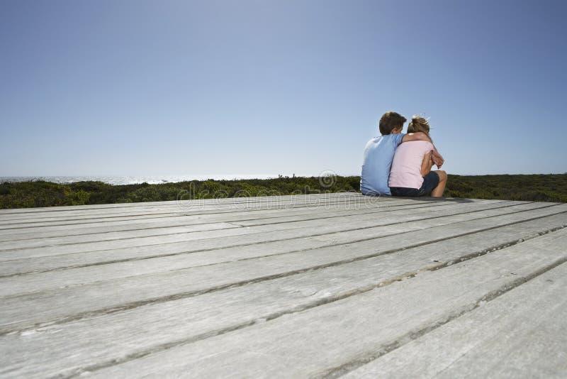 女孩和男孩坐木板走道 免版税图库摄影