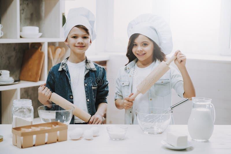 女孩和男孩开始画象烹调在厨房的 免版税库存照片