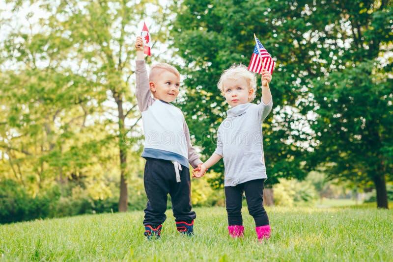 女孩和男孩微笑的笑握手和挥动美国和加拿大旗子,外部在公园 图库摄影