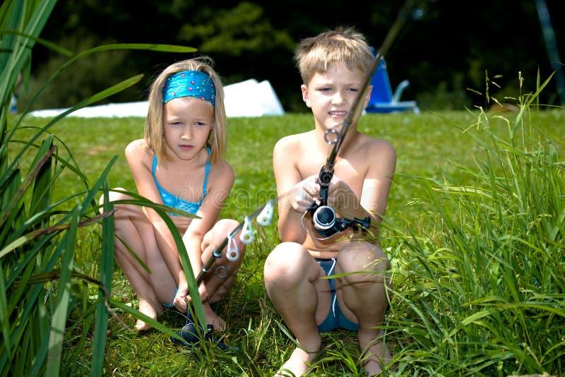 女孩和男孩捕鱼 免版税库存图片