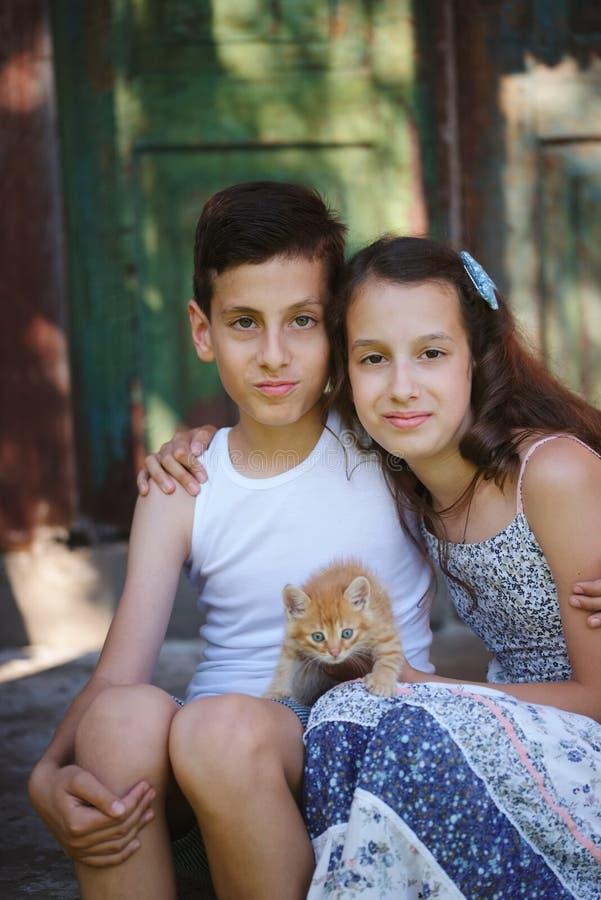 女孩和男孩有红色小猫的 免版税库存照片
