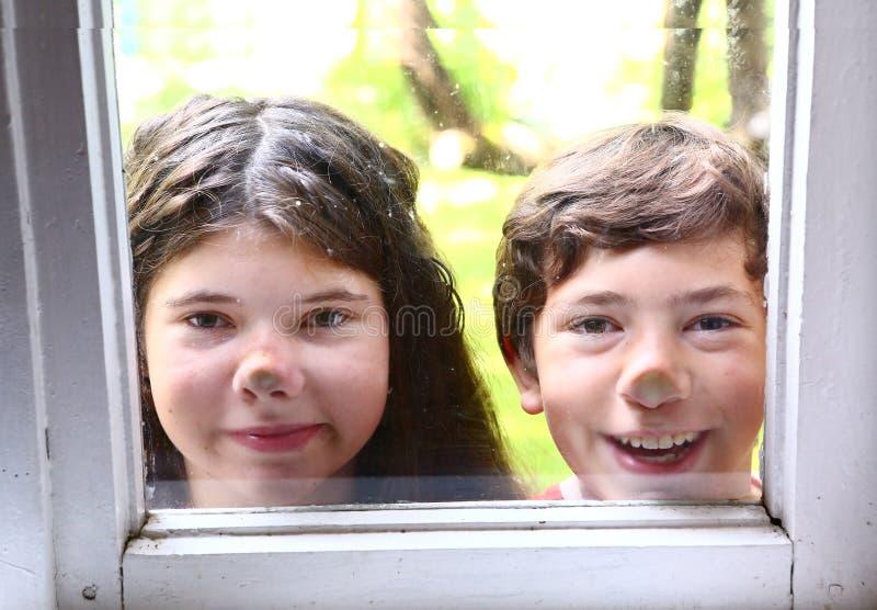 女孩和男孩有鼻子的按了反对窗口 免版税库存照片