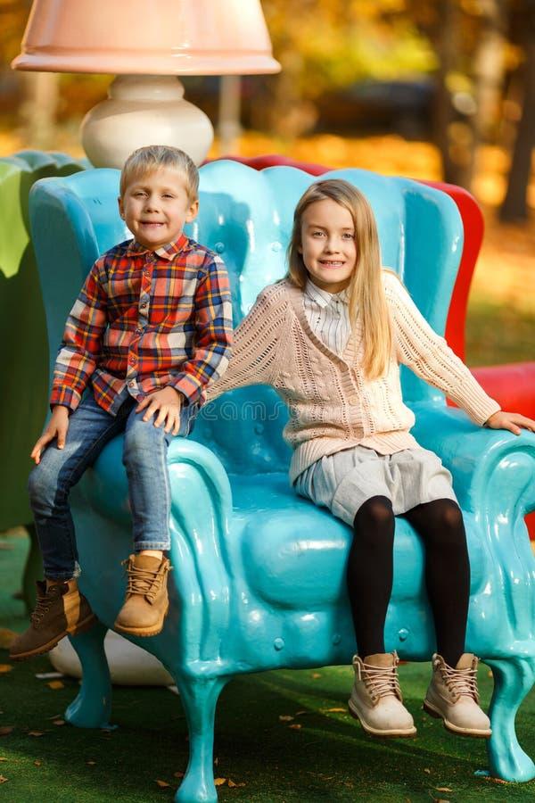 女孩和男孩照片坐蓝色扶手椅子在秋天公园 图库摄影