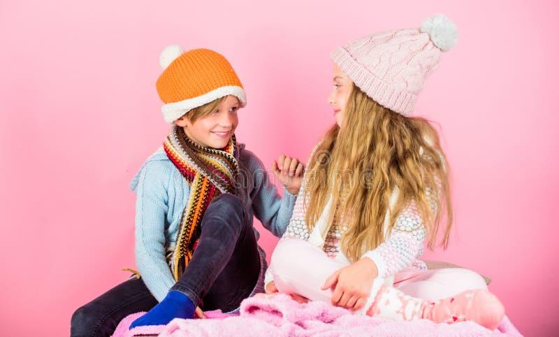 女孩和男孩穿戴被编织的冬天帽子 冬天季节时装配件和衣裳 孩子编织了冬天帽子 孩子 库存图片
