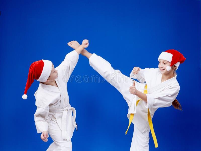 女孩和男孩训练被配对的锻炼空手道 库存图片