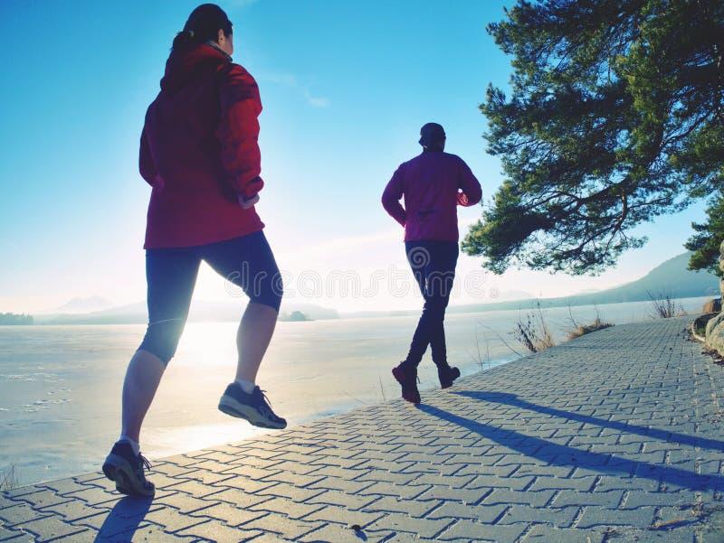 女孩和男孩赛跑,当太阳做在冻结的湖表面时的反射 免版税库存图片