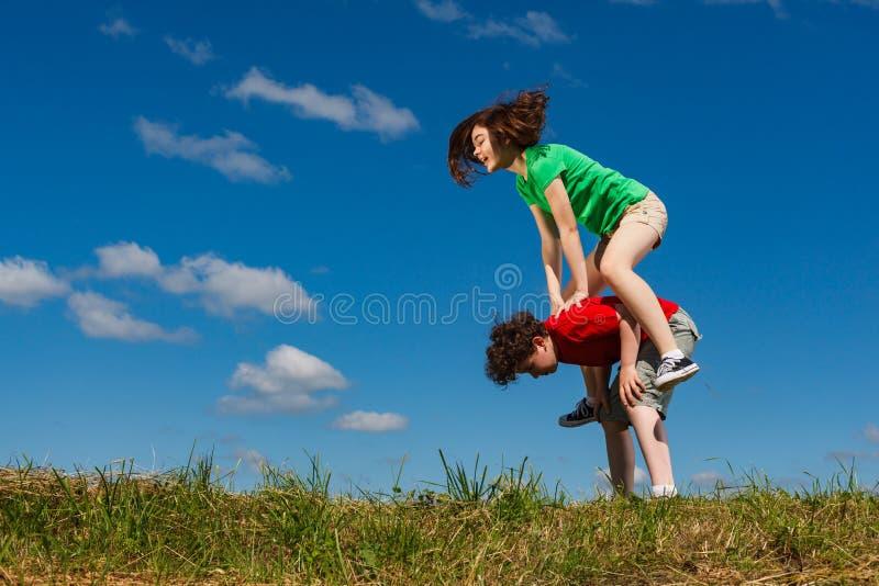女孩和男孩跳跃室外 库存图片