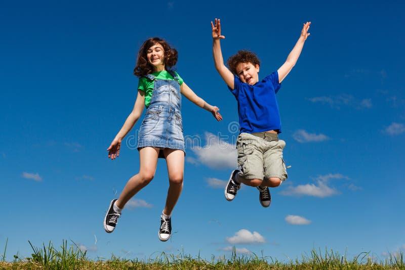 女孩和男孩跳跃室外 免版税库存照片