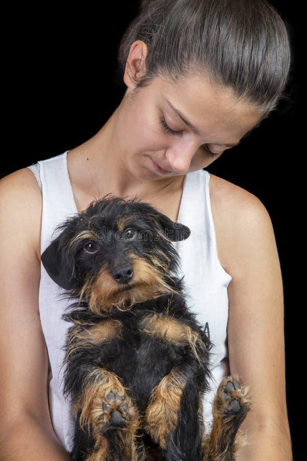 女孩和硬毛的达克斯猎犬在黑背景 免版税库存照片